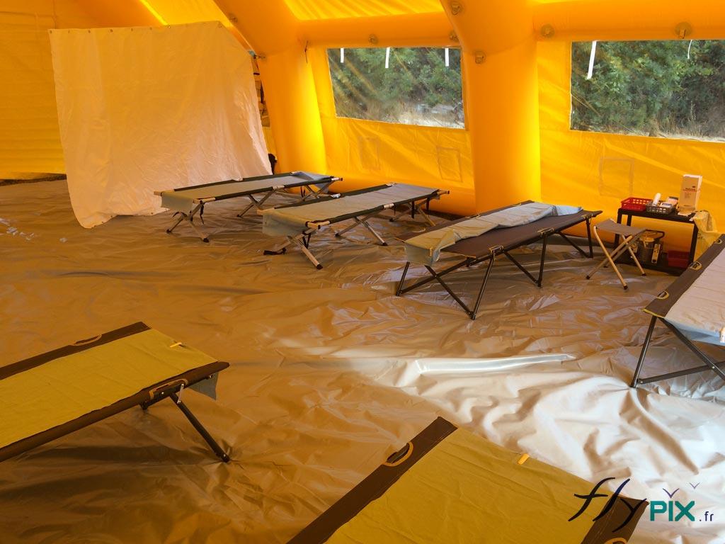 Intérieur spacieux d'un abri gonflable PMA, avec une bâche au sol, et des brancards prêts à accueillir des patients.