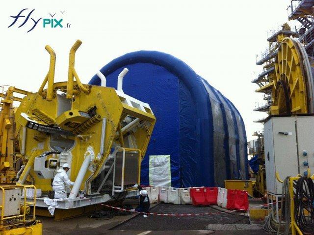 Un hangar gonflable en forme de U inversé, la machine jaune devant la porte devra être nettoyée à l'intérieur.