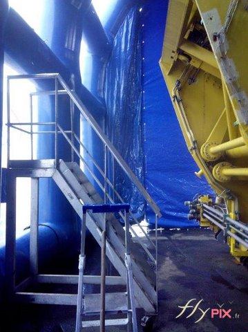 Un hangar gonflable avec à l'intérieur une machine industrielle à nettoyer ou à réparer, à l'abri des intempéries.