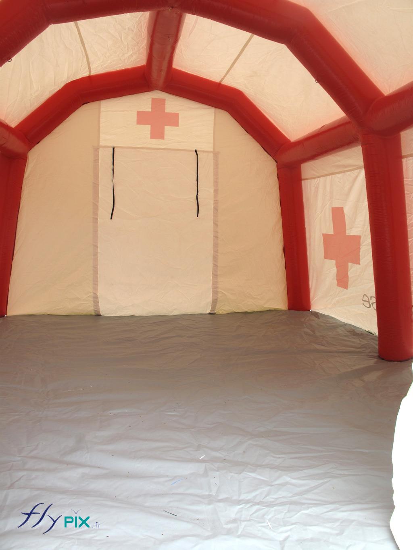 Vue depuis l'intérieur de la tente médicale de premiers secours: bâche au sol lavable et large porte pignon fixée par bande velcro.