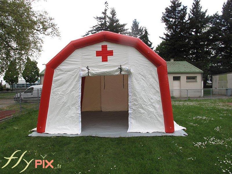 Vue de face d'une tente PMA gonflable, avec la porte d'accès à pignon et large, pour faciliter la venue des patients ou des malades.