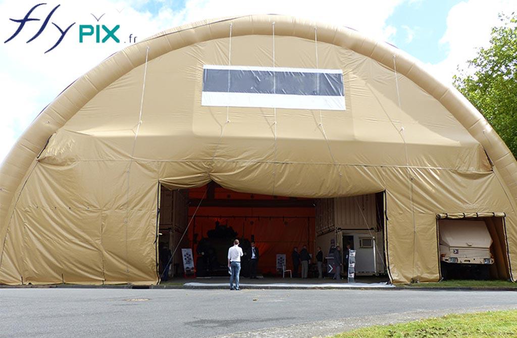 Hangar gonflable industriel, en forme de tunnel, avec une large ouverture, pour faire circuler des machines ou des véhicules.