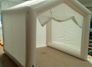 Tente gonflable en forme de maison, avec des grandes ouvertures, pour des chantiers de menuiserie, pour la pose de portail, en extérieur.