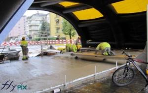 Tente de chantier gonflable: des ouvriers travaillent la pose de béton au sol, en étant protégé de la pluie et des intempéries.