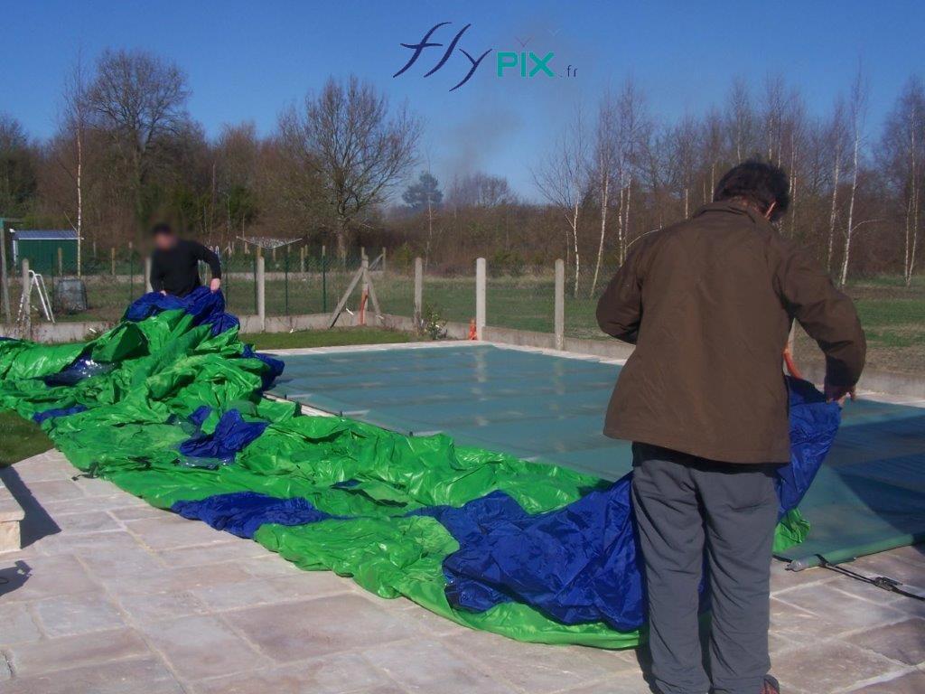 Session de dépliage d'un abri piscine gonflable.