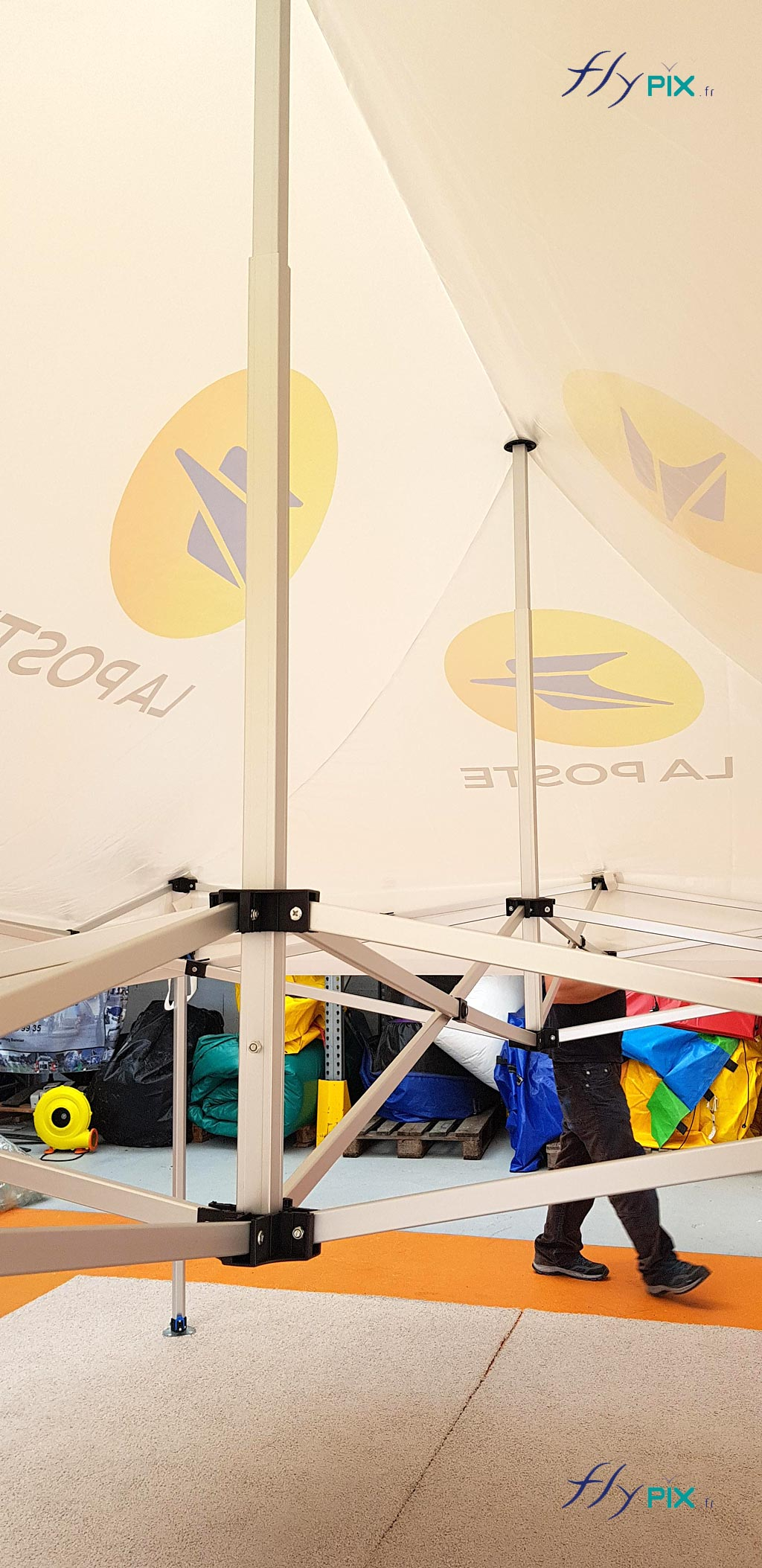 Vue intérieure d'une tente pliable: armatures en métal et enveloppe en toile enduite de PVC.