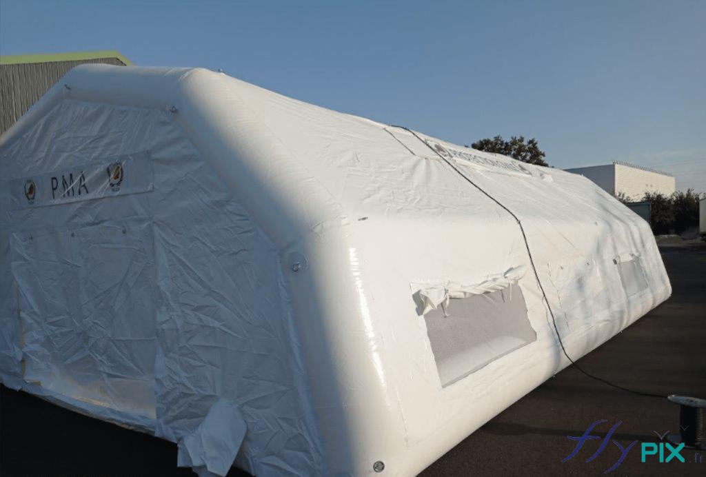 Tente médicale comprenant: des larges portes pignon, des fenêtres avec volets et moustiquaires, des manchons à air et passe fils électriques.