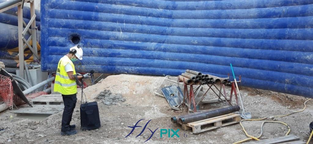 Un technicien de chantier urbain, en ville, se prépare à manipuler une machine au milieu des murs anti-acoustiques de réduction de bruits.