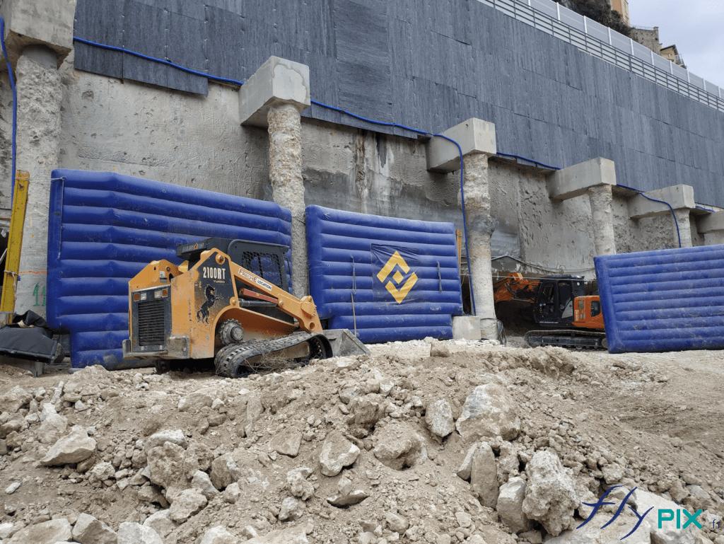 Plusieurs segments de murs gonflables de réduction de bruits (anti-acoustiques), disposés à plusieurs endroits du chantier en ville.