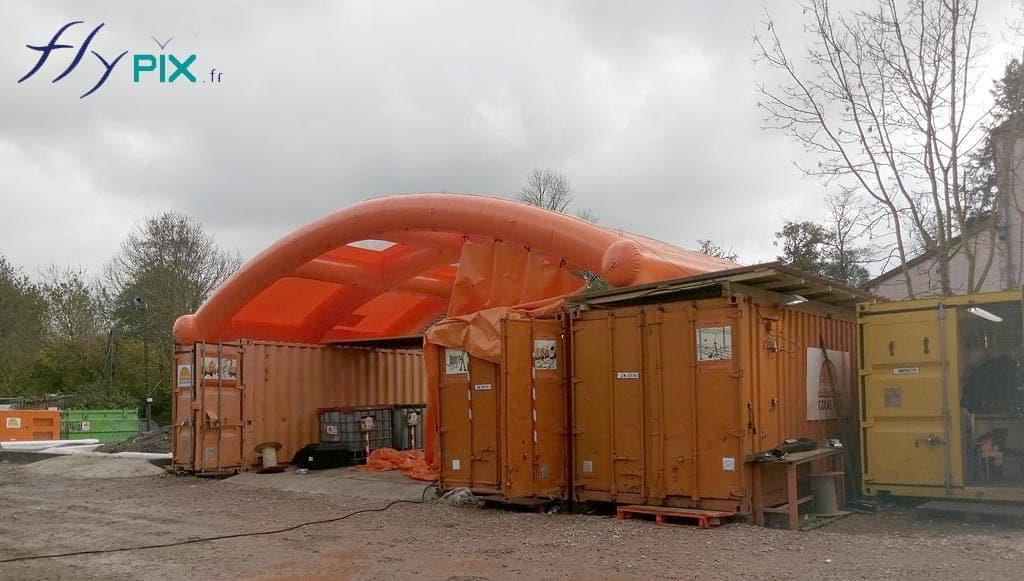 Un préau gonflable air captif, en enveloppe PVC 0.6 mm, déployé entre 2 containers maritimes.