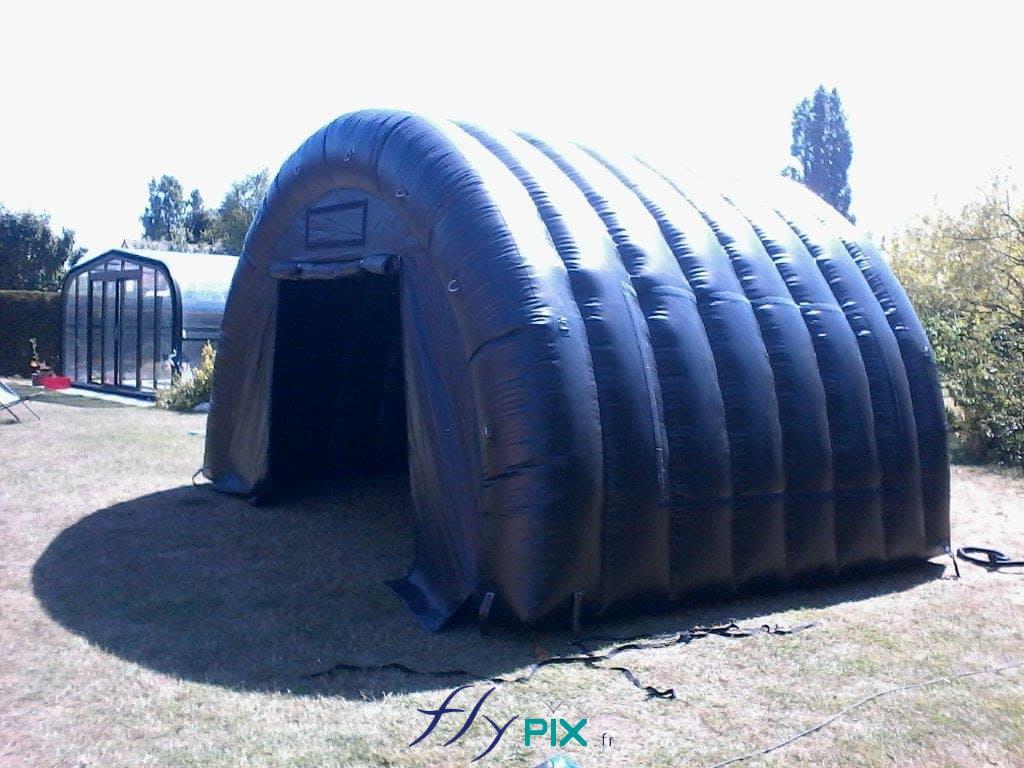 Une tente gonflable tunnel demi-lune, de couleur bleue, utilisée pour le stockage de matériel ou de machines.