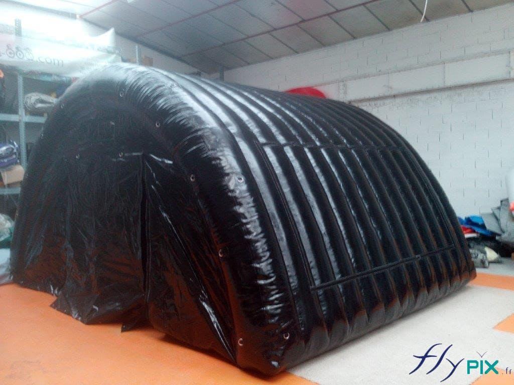 Une tente gonflable tunnel de stockage de matériel, en forme de demi-lune, et avec une enveloppe PVC 0.6 mm double peau de couleur noire.